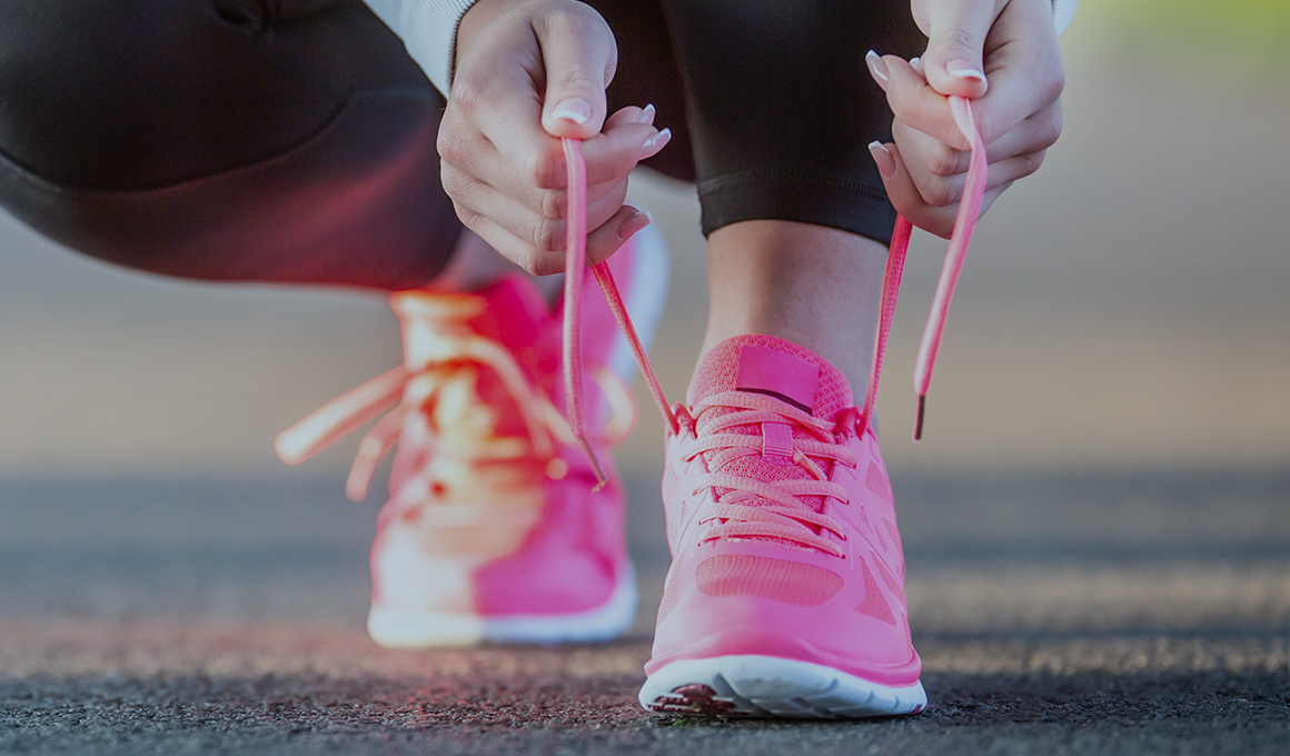 Female crouching down tying the laces on bright pink running shoes