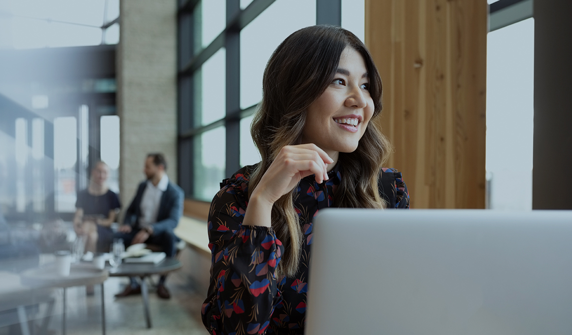 Woman with long wavy hair sitting in front of laptop in a lobby, looking away from the camera, smiling. She is in focus while the people in the background are out of focus.