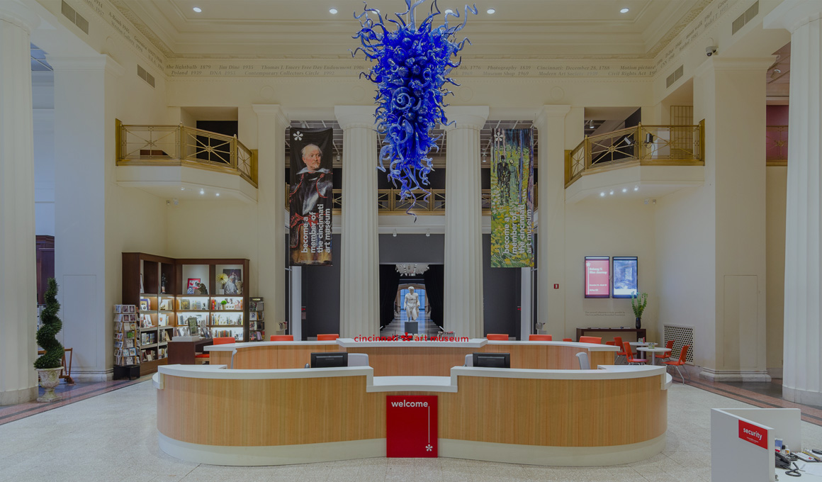 The welcome desk in the lobby at the Cincinnati Art Museum sits below a blue Chihuly sculpture hanging from the very tall ceiling.