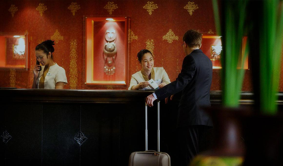 Two receptionists sit behind the welcome counter in an IHG hotel. One is speaking on the phone while the other smiles at an unrecognizable customer.
