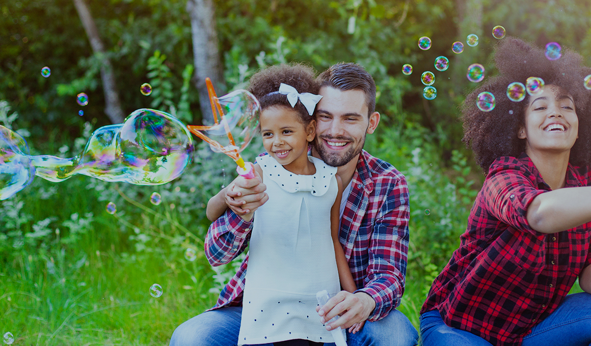 A husband and wife with their daughter, all smiling while using bubble wands outside.