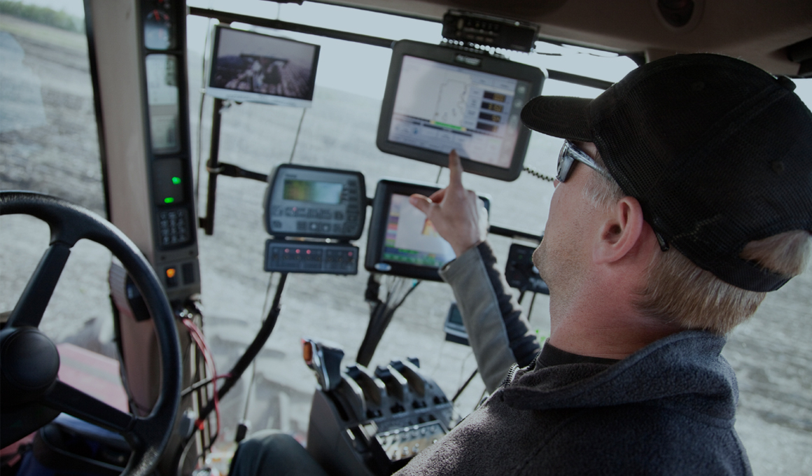 Middle-aged man sitting inside a large piece of farming equipment. He is facing away, pointing to one for 2 touch screens.