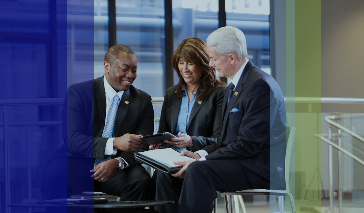Three Fifth Third Bank associates discussing unknown details on a tablet.