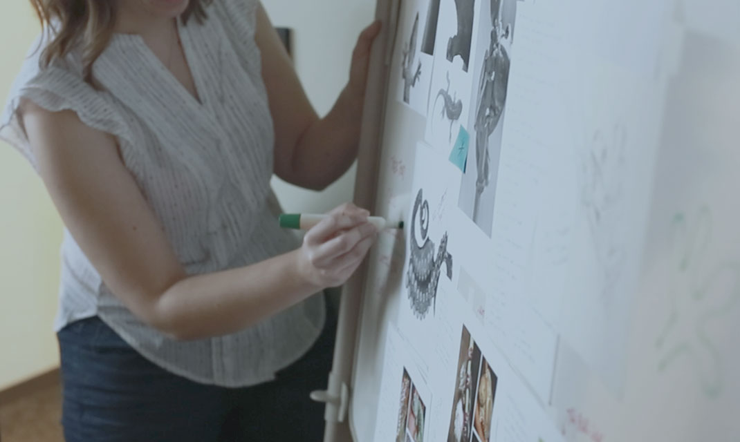 Photo of a woman sketching on a whiteboard with illustrations