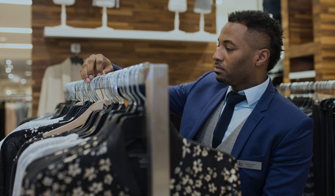 A well-dressed, Black, male Bloomingdale's sales associate concentrating on organizing a rack of clothing on the sales floor.